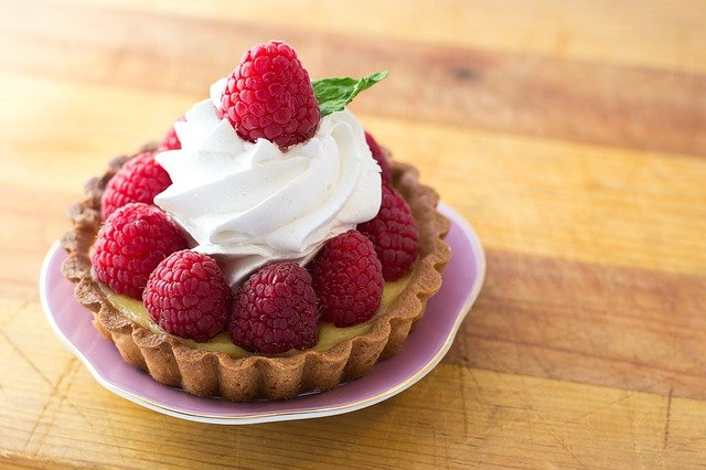Raspberry tart with whipped cream in a dish on a wooden table