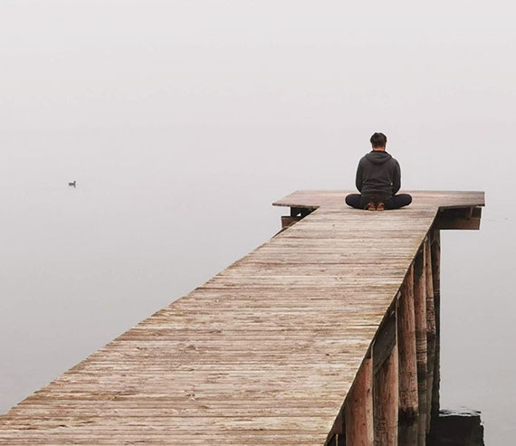 Man at the end of a dock over a misty lake, sitting on his shoes, meditating