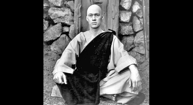"""David Carradine as Kwai Chang Caine from """"Kung Fu"""" seated on the ground in robes in front of a stone wall"""