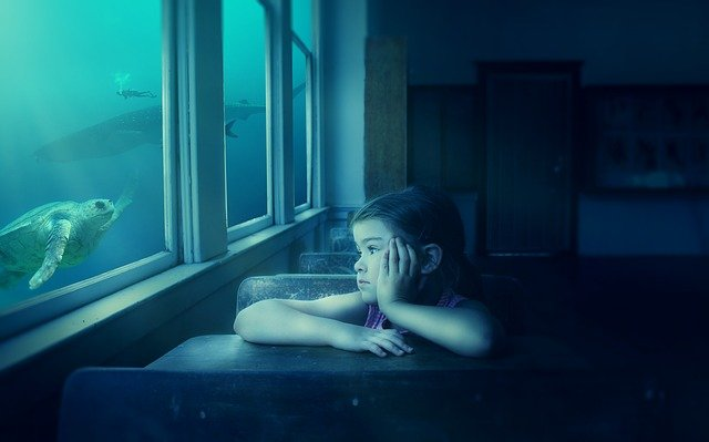 Little girl in a classroom stares out the window into an undersea scene featuring a turtle, whale, shark, and scuba diver