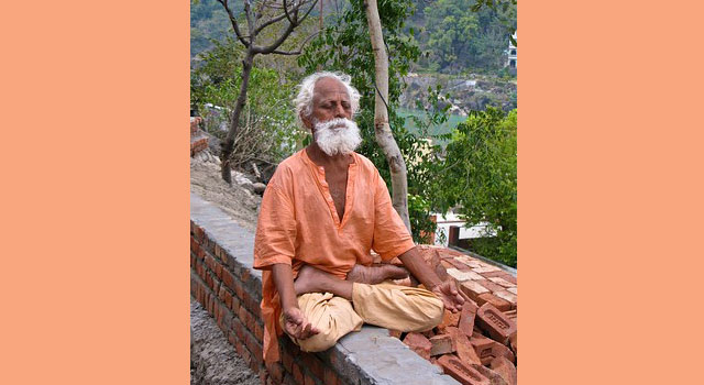 An elderly man sits in full lotus posture atop a small stone wall along a road above the Ganges River.