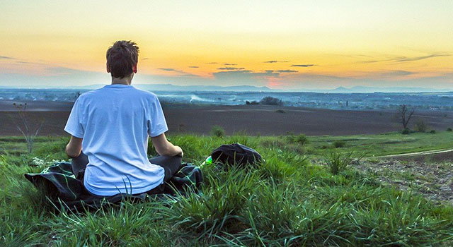 A young man seen from behind, sitting on the grass looking toward distant mountains at sunset