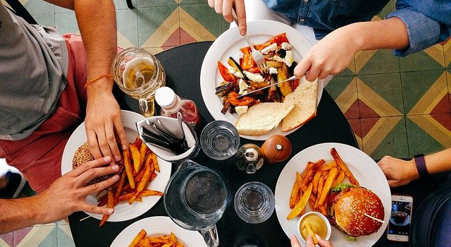 Four people at a restaurant table, three eating burgers and fries, one eating roasted vegetables and bread.