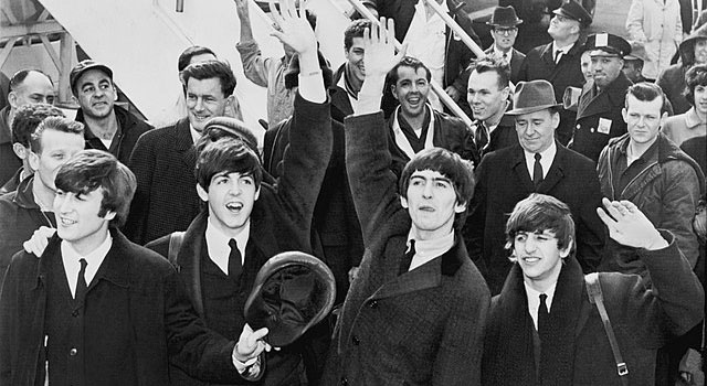 The Beatles wave to fans on the tarmac of JFK airport in 1964