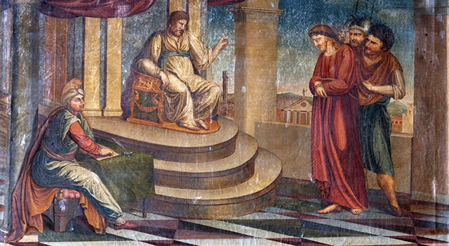 Pilate, seated on a dais, raises a hand toward Jesus, who is standing while being held by two guards, as a scribe seated at a table takes notes.