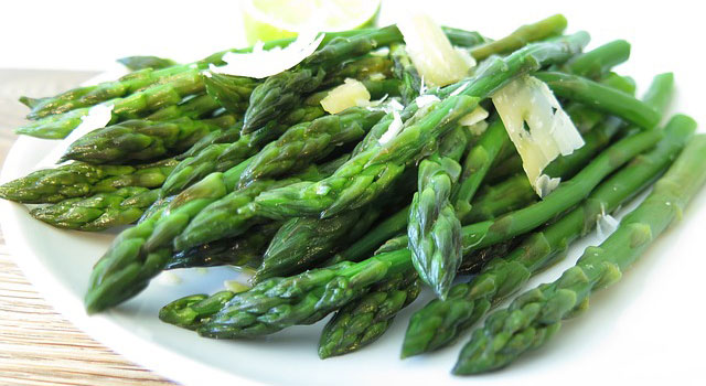 Asparagus on a plate with shaved Parmesan cheese