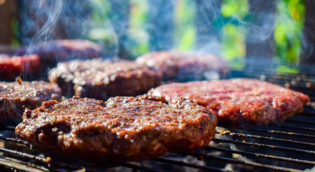 Hamburger patties cooking on a charcoal grill