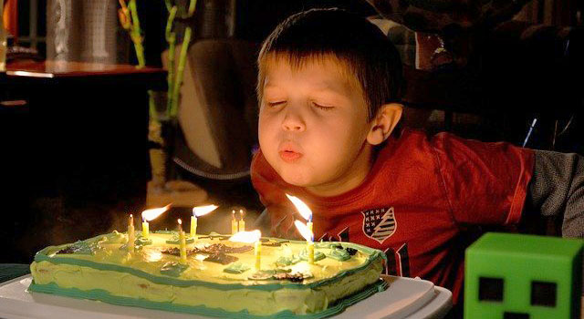 Boy blowing out candles on a birthday cake