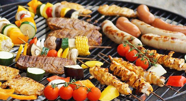Steaks, sausages, and kabobs on a charcoal grill