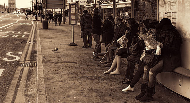 Several people waiting at a bus stop