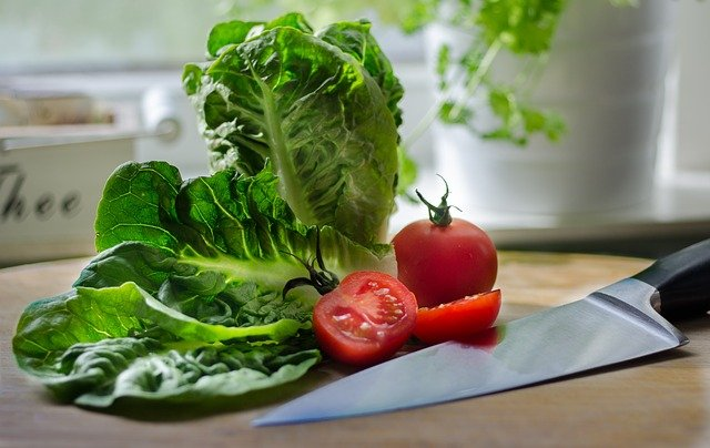 Lettuce leaves and sliced tomato on a kitchen counter