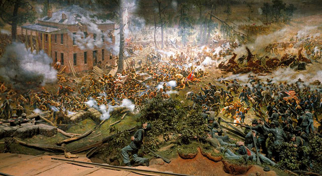 A scene from the Atlanta Cyclorama depicting scale models of troops fighting near a railroad track, and behind them a painting of more troops fighting around a two-story brick building flanked by pine trees.