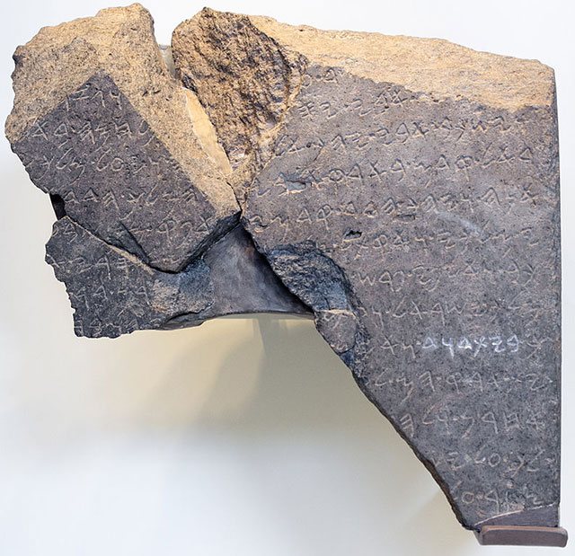 Three pieces of broken stone from an ancient monument placed back together, showing an inscription across the surface