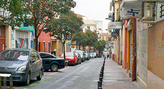A narrow one-way street in the Bellas Vistas neighborhood of Madrid lined with first-floor shops and apartments in upper stories, with cars parked beneath small trees on one side and a brick sidewalk on the other