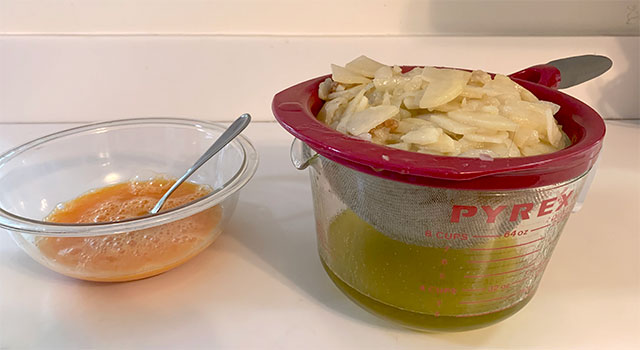 Beaten eggs in a bowl on a countertop beside a colander of sliced potatoes and onions draining into a one-quart Pyrex measure