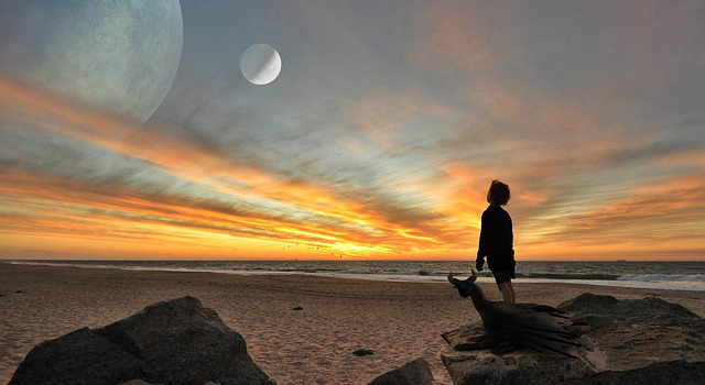 A boy stands on a beach at sunrise looking into a sky with two large moons