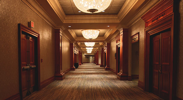 Interior corridor of a hotel with wood paneled doors, tray ceilings, and large overhead dome lights