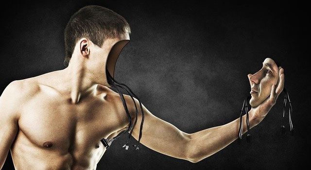 A shirtless man who has removed his own face, revealing a cavity with wires inside, and is holding it in his outstretched hand facing his body