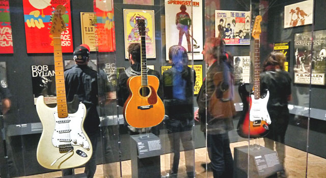 Jimi Hendrix' white Stratocaster, Eric Clapton's Martin acoustic, and Bob Dylan's sunburst Stratocaster on display at the Met