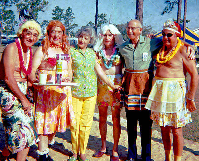 A half dozen senior citizens, five men and a woman, pose at an Airstream park. The woman at center left wears brightly colored pants and blouse. The men are partially or entirely in women's clothing, and one is balancing three cans on a tray which also holds a drinking cup. Behind them are Airstream trailers, pine trees, and a yellow and blue canopy.