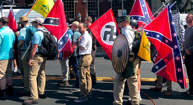 Men lined up in the street, holding Gadsden flags, Nazi flags, and rebel flags