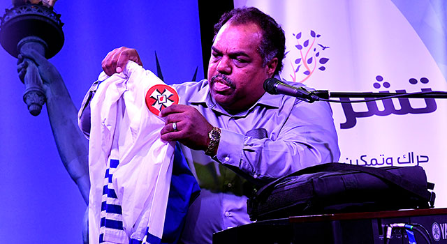 A man seated on a stage, wearing a blue button-down shirt, holds up a white robe adorned with emblems of the Ku Klux Klan
