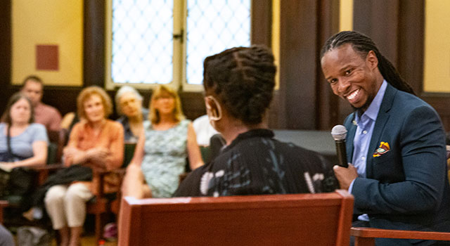 Professor Ibram X. Kendi sits with a microphone, smiling and looking at an unidentified speaker (seen from behind) in a church with a small audience in the background.