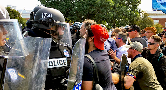 Police in riot gear hold back a crowd of men